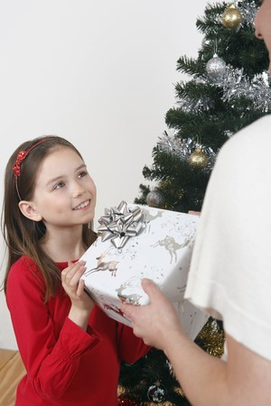 Girl receiving Christmas present from woman photo