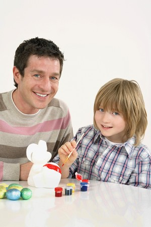 Boy painting clay rabbit with man sitting beside him photo