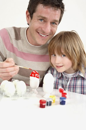 Man painting Easter eggs with boy sitting beside him photo