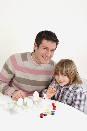 Man and boy painting Easter eggs together photo