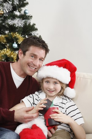 Man and boy opening Christmas presents together photo
