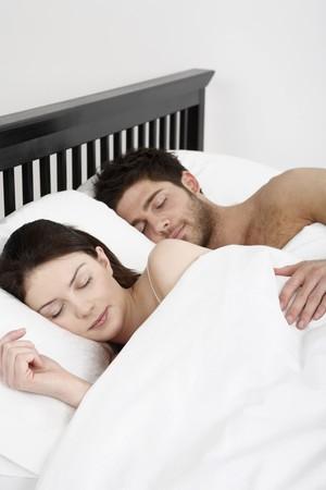 El hombre y la mujer en la cama para dormir juntos Foto de archivo