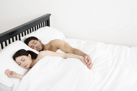 Man and woman sleeping together in bed photo