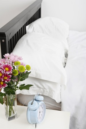 A vase of flowers and alarm clock beside a bed photo