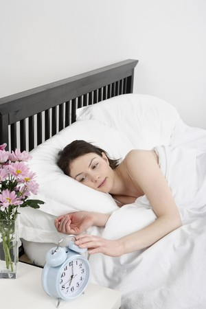 bedside: Woman lying in bed, turning off the alarm clock