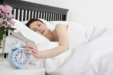 Woman lying in bed, turning off the alarm clock photo