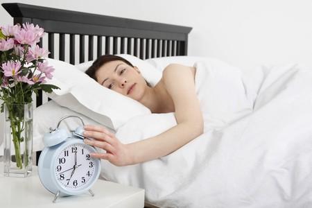 目覚まし時計を回す、ベッドで横たわる女 写真素材