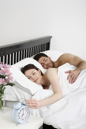 turning table: Man and woman lying in bed, woman turning off the alarm clock
