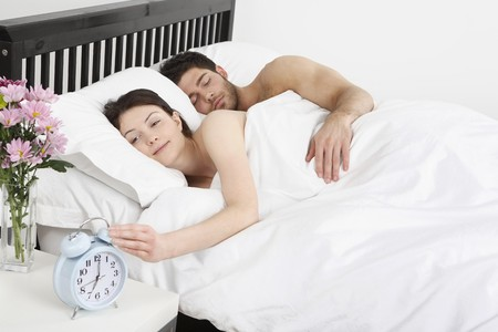 bedside: Man and woman lying in bed, woman turning off the alarm clock