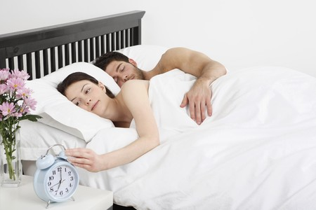 Man and woman lying in bed, woman turning off the alarm clock photo