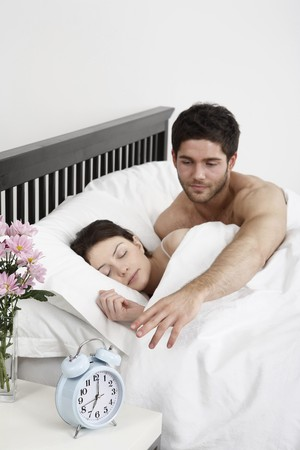 Woman sleeping, man reaching out to turn off the alarm clock photo