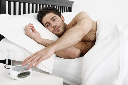 bedside: Man lying in bed, turning off the alarm clock Stock Photo