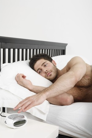 Man lying in bed, turning off the alarm clock photo