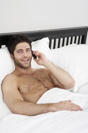 english ethnicity: Man lying in bed, talking on the phone Stock Photo