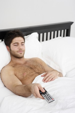 changing channel: Man lying in bed, changing channel with remote control