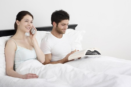 Woman talking on the phone, man reading book in bed Stock Photo - 4109721