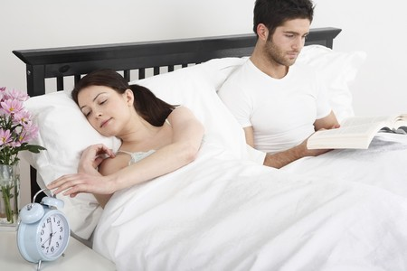 Woman turning off the alarm clock, man reading book in bed photo