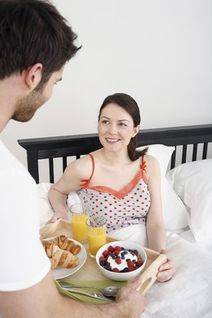 Man serving woman with breakfast in bed