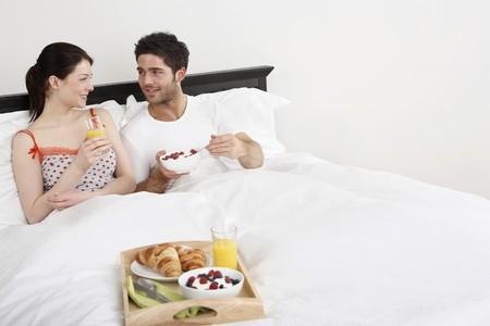 El hombre y la mujer gozan de desayuno en la cama