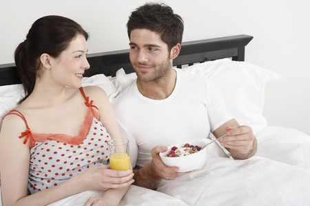 Man and woman enjoying breakfast in bed photo