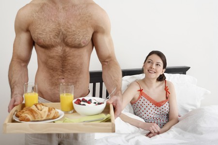 Man holding a tray of breakfast, woman smiling while watching photo