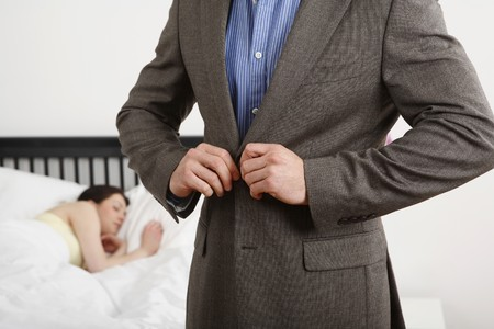 Man buttoning his coat, woman still in bed
