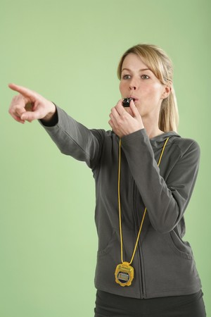 Woman blowing whistle while pointing forward