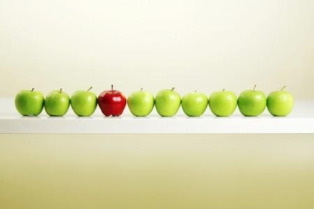 Manzana roja entre una fila de manzanas verdes