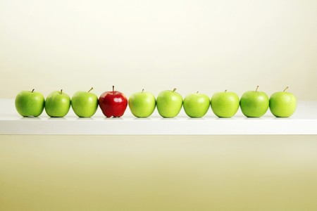 Red apple among a row of green apples