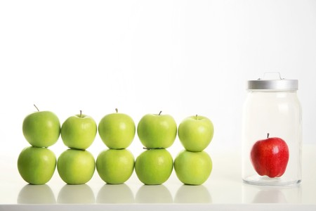 individualism: Green apples stacked on top of each other with red apple in a jar beside them Stock Photo