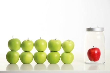 Manzanas verdes apilados uno encima del otro con manzana roja en un frasco junto a ellos