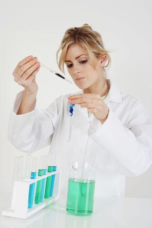 Mujer en bata de laboratorio llevar a cabo un experimento de ciencia Foto de archivo