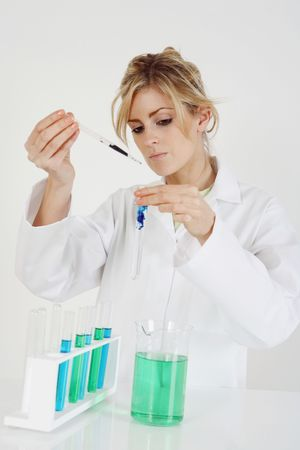 test tube holder: Woman in lab coat carrying out a science experiment Stock Photo