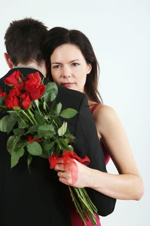 Man and woman embracing, woman holding bouquet of flowers photo