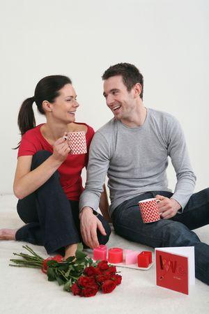 Hombre y mujer conversando mientras disfrutan sus bebidas