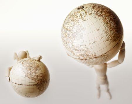 Ficticio levantamiento mundo mientras que otro maniquí con las manos en globo Foto de archivo