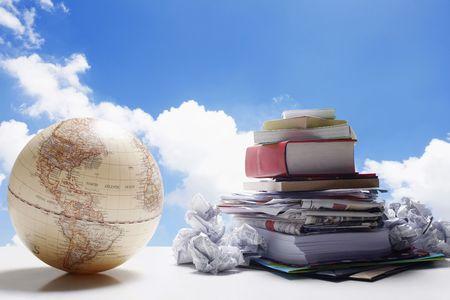 Mundo al lado de una pila de papeles, libros, periódicos y documentos arrugado