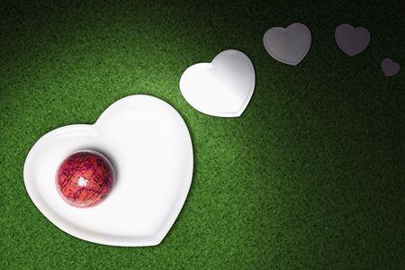 Mundo en miniatura de color rojo en forma de corazón sobre la placa