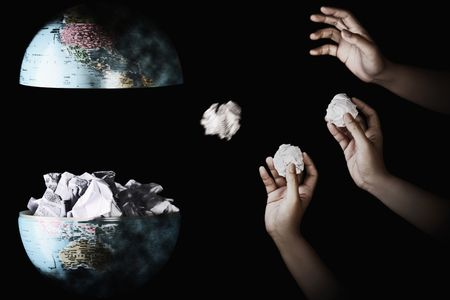 Human hand throwing crumpled paper into the center of globe Stock Photo