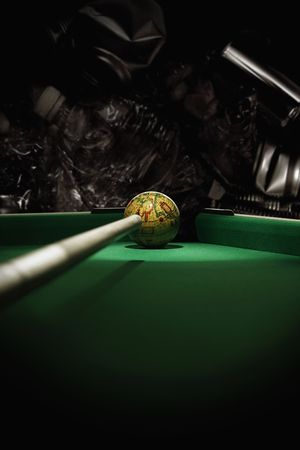 Snooker cue aiming at miniature globe with plastic bottles and tin cans in the background
