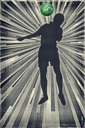 heading the ball: Silhouette of a footballer heading a Brazil flag ball