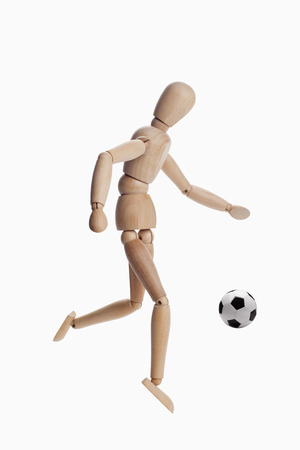 Wooden dummy model playing soccer photo