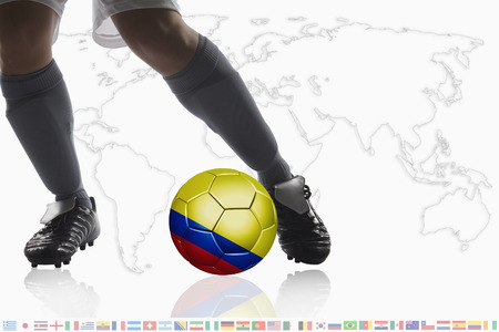 Soccer player dribble a soccer ball with Colombia flag photo