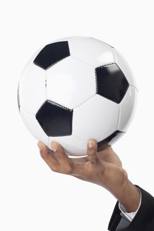 Soccer manager holding a ball with one hand