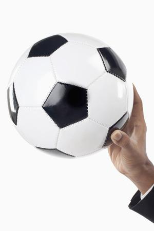Encargado del fútbol que sostiene un balón con una mano