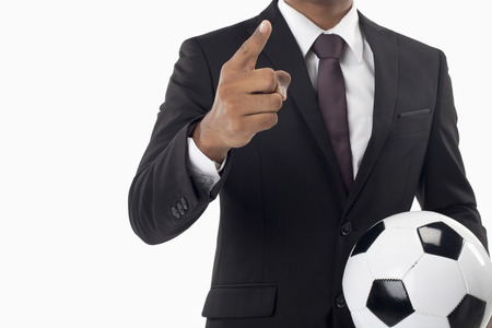 Soccer manager holding a ball and pointing photo