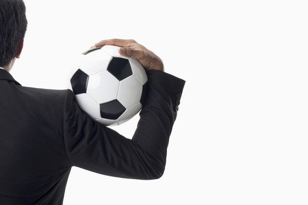 Soccer manager holding a ball on his shoulder photo