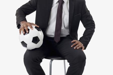 Soccer manager holding a ball on his lap photo