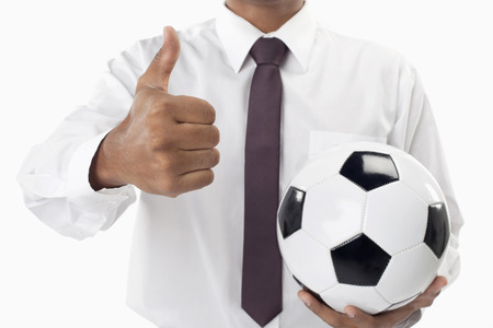 Soccer manager holding a ball and thumbs up photo
