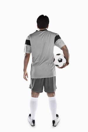 back shots: A soccer player holding a ball